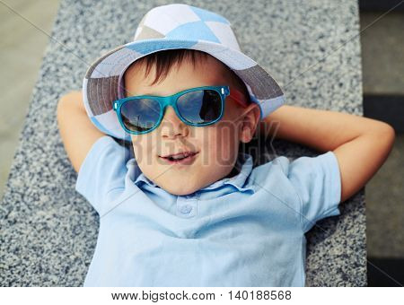 Joyful small boy in sunglasses is resting with hands under his head on street stairs parapet