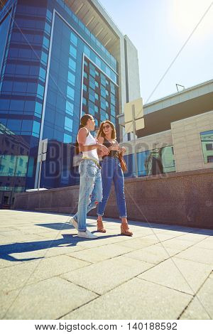 Two young beautiful females in casual summer clothes are walking along the street and chatting in downtown on warm sunny day