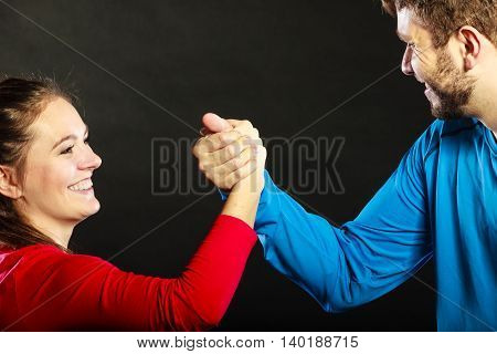 Happy friends young man and woman clasping shaking hands. Handshake greeting gesture in studio on black.