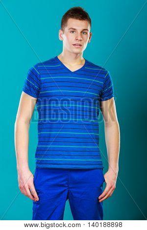 Young man teen boy portrait studio shot on blue background