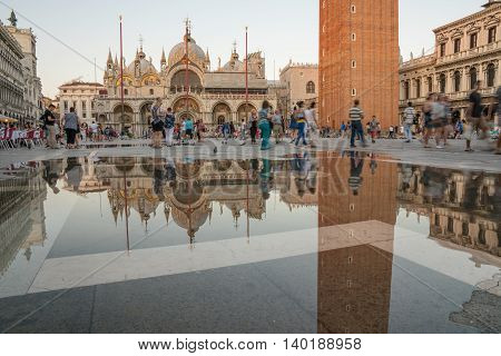 VENICE ITALY - JULY 1 2016: Tourists in San Marco square in front of St. Mark's Basilica in Venice Italy as water water risesin the square.