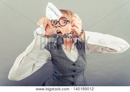 Business and stress concept. Furious businesswoman in glasses with chained hands holding contract grunge background unusual angle view