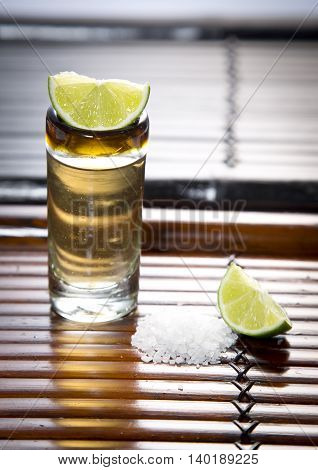 a small glass of tequila with salt and lemon