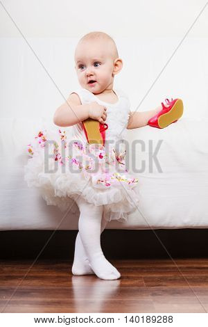 Lesson of walking. Sweet adorable baby girl making steps at home. Little child toddler wearing princess dress with red small shoes.