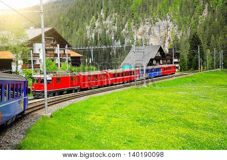Passenger train approaches to the railway station. Swiss Alps.