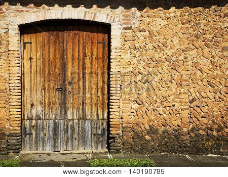 Grunge stile of brick wall and wood door vintage in old town on Mexico.