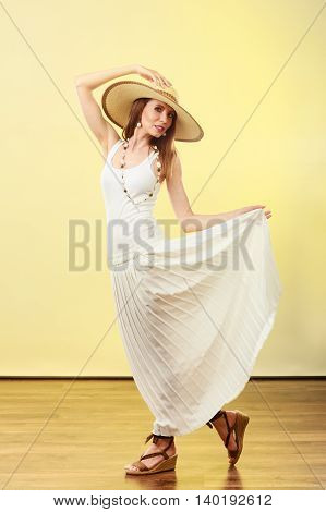 Holidays and summer fashion. Woman wearing big straw hat white dress. Female model posing in full length on bright yellow background.