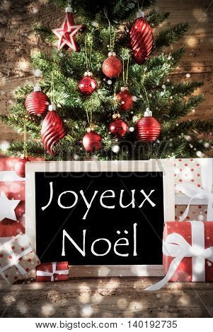 Christmas Tree With Balls And Snowflakes. Gifts Or Presents In The Front Of Wooden Background With Bokeh Effect. Chalkboard With French Text Joyeux Noel Means Merry Christmas