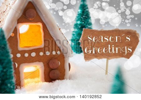 Gingerbread House In Snowy Scenery As Christmas Decoration. Christmas Trees And Candlelight For Romantic Atmosphere. Silver Background With Bokeh Effect. English Text Seasons Greetings