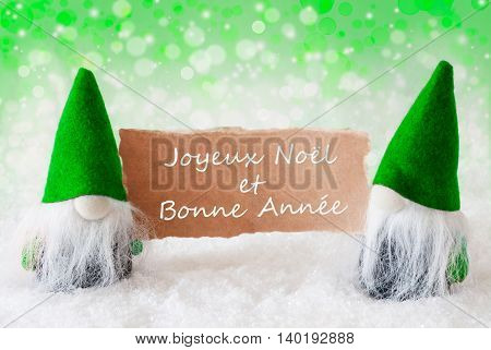 Christmas Greeting Card With Two Green Gnomes. Sparkling Bokeh And Natural Background With Snow. French Text Joyeux Noel Et Bonne Annee Means Merry Christmas And Happy New Year