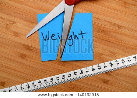 weight loss concept - scissors cutting note