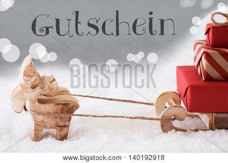 Moose Is Drawing A Sled With Red Gifts Or Presents In Snow. Christmas Card For Seasons Greetings. Silver Background With Bokeh Effect. German Text Gutschein Means Voucher