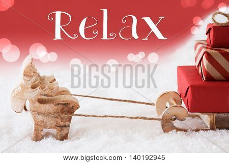 Moose Is Drawing A Sled With Red Gifts Or Presents In Snow. Christmas Card For Seasons Greetings. Red Christmassy Background With Bokeh Effect. English Text Relax