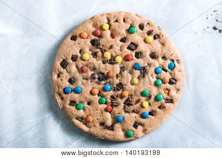Big homemade chocolate chip cookie with colorful bonbons