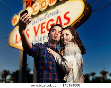 couple taking selfies in front of lit up las vegas sign at night