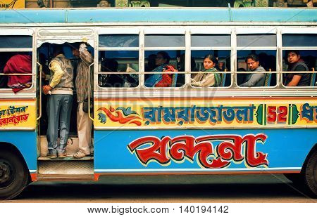 KOLKATA INDIA - JANUARY 13, 2013: Colorful bus driving on indian street and many different people inside of it on January 13, 2013 in India. Kolkata has a density of 814.80 vehicles per km road length