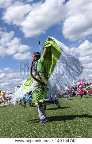 Coeur d'Alene Idaho USA - 07-23-2016. Young native woman spreading arms at dance. Young dancer participates in the Julyamsh Powwow on July 23 2016 at the Kootenai County Fairgrounds in Coeur d'Alene Idaho.