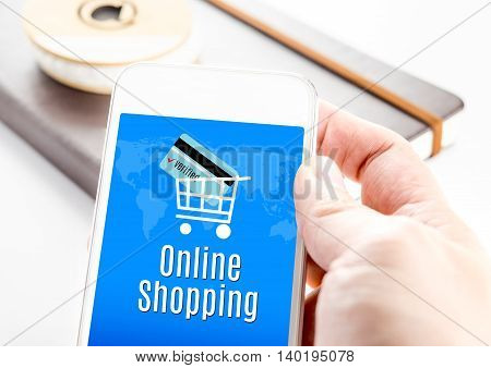 Close up hand holding smartphone with Online shopping word and credit card in cart icons Business Marketing concept.