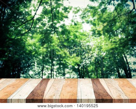 Empty Perspective Tropical Wood Table With Blurred Green Tree Forest,template Mock Up For Display Of