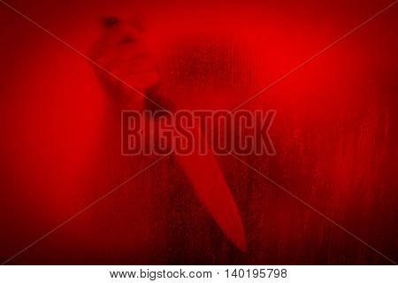 Horror scene of woman with knife behind stained or dirty window glass,Serial killer or violence concept background