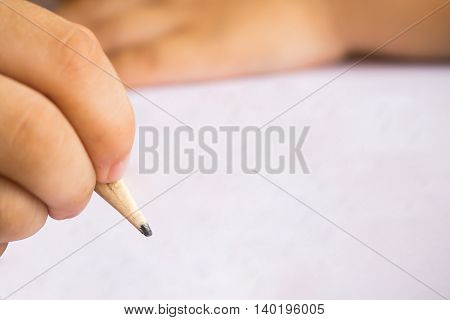 boy write note on white paper with pencil