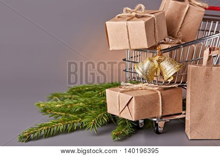 Shopping trolley with gift boxes and brenches of fir-tree on a grey background. Christmas and New Year sale.