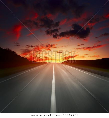 Blurred asphalt road and sky with red clouds