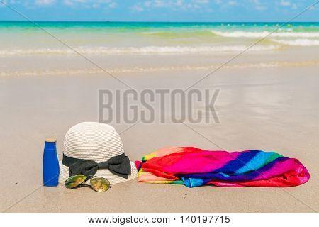Sunglasses, sun cream and hat  on white  sand beach