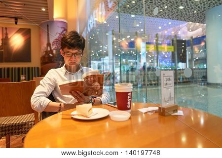 SHENZHEN, CHINA - CIRCA MAY, 2016: indoor portrait of a man at Costa Coffee. Costa Coffee is a British multinational coffeehouse company.