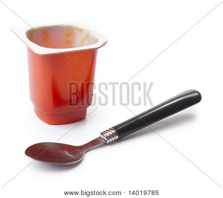 Empty yougurt pot and spoon over white