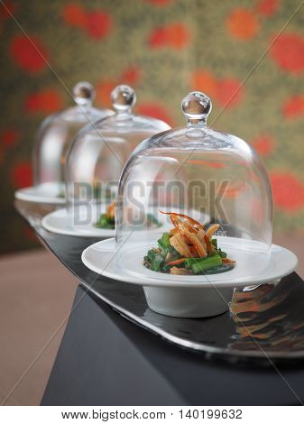 Seafood salad in glass cover in white plate in asian restaurant