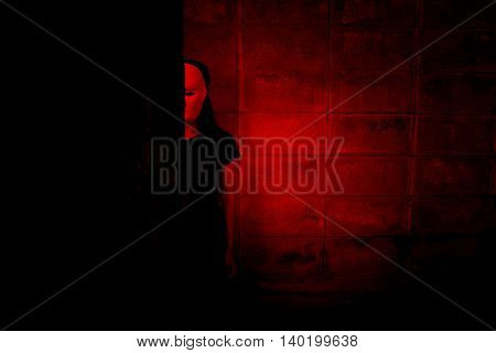 Mysterious woman in black dress wearing white mask hiding behind tree,Scary background for halloween