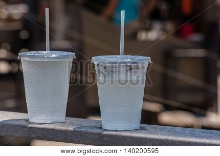 Two cold carbonated drinks in transparent plastic cups