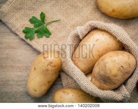 Closeup Fresh Organic Potatoes In Hemp Sake Bag With Parsley On Rustic Wooden Table Preparation For