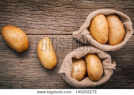 Fresh Organic Potatoes In Hemp Sake Bag On Rustic Wooden Background. Row Organic Potatoes  On Old Wo