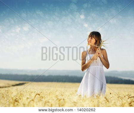 Young smiling woman in white dress standing in field