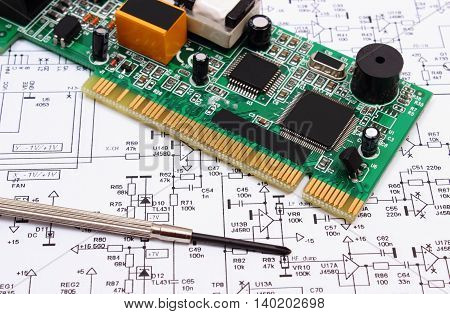 Printed circuit board with electrical components and precision screwdriver lying on construction drawing of electronics accessories for engineer jobs technology