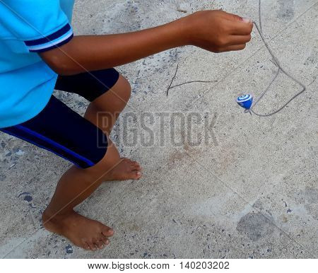 arm and lower part of Thai child seen flipping a spinning homemade wooden top into the air with a loop of string, paved playground near Songkhla, Thailand