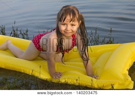little white girl children posture on yellow inflatable mattress on lake