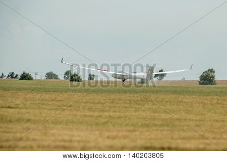The glider landed on the grassy airport