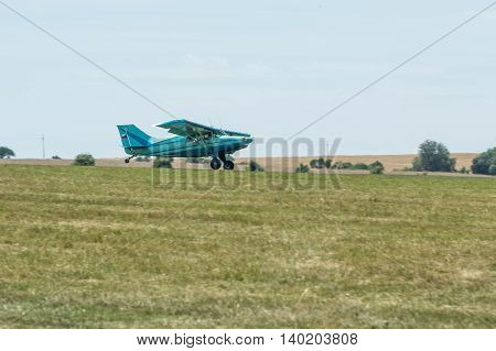 Small blue tow plane landing on a grassy airfield.