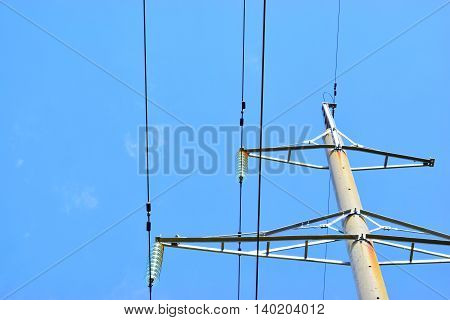 High-voltage power support with wires against blue sky.