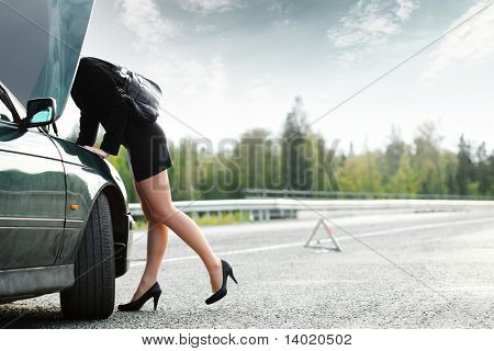 Young woman with heels repairing her broken car
