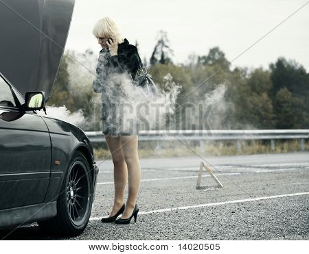 Young woman talking on mobile phone near broken and smoking car
