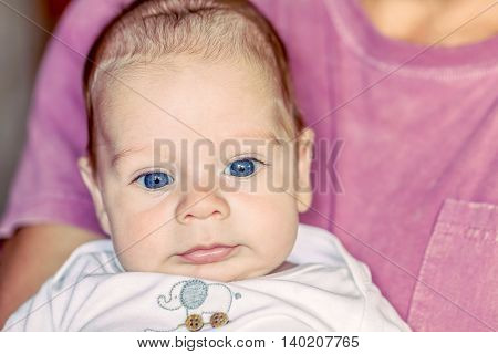 Portrait Of Cute 4-Month Newborn Baby Boy With Powerful Blue Eyes Lying On Father Arms