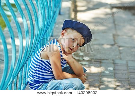 Portrait of a beautiful boy in a city Park . Dressed in a nautical style .
