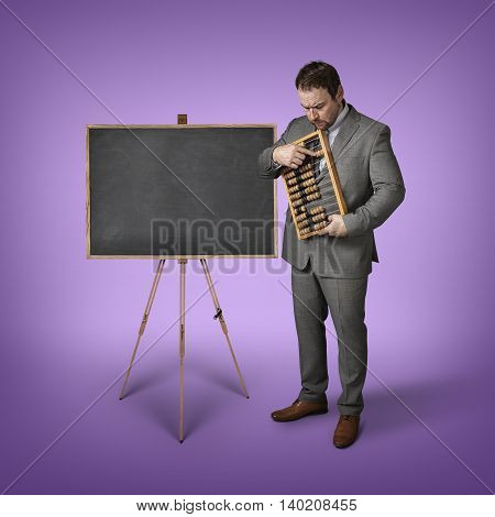 Businessman with abacus and blackboard at office