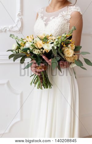 bride holding a bouquet of flowers in a rustic style wedding bouquet. Bride with bouquet in the white room