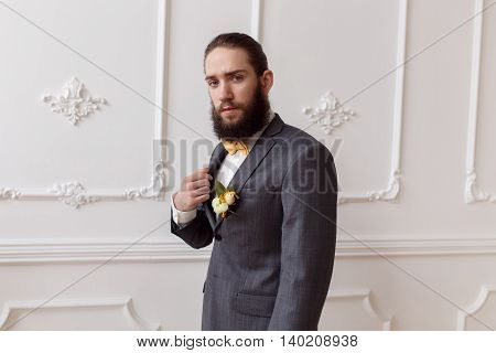 Handsome strong brutal bearded groom posing in suit with orange bow on a light background