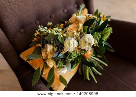Bridal bouquet. The bride's bouquet. Beautiful bouquet of white peonies cream roses and greenery decorated with orange silk ribbon lies on the orange cushions background in brown chair